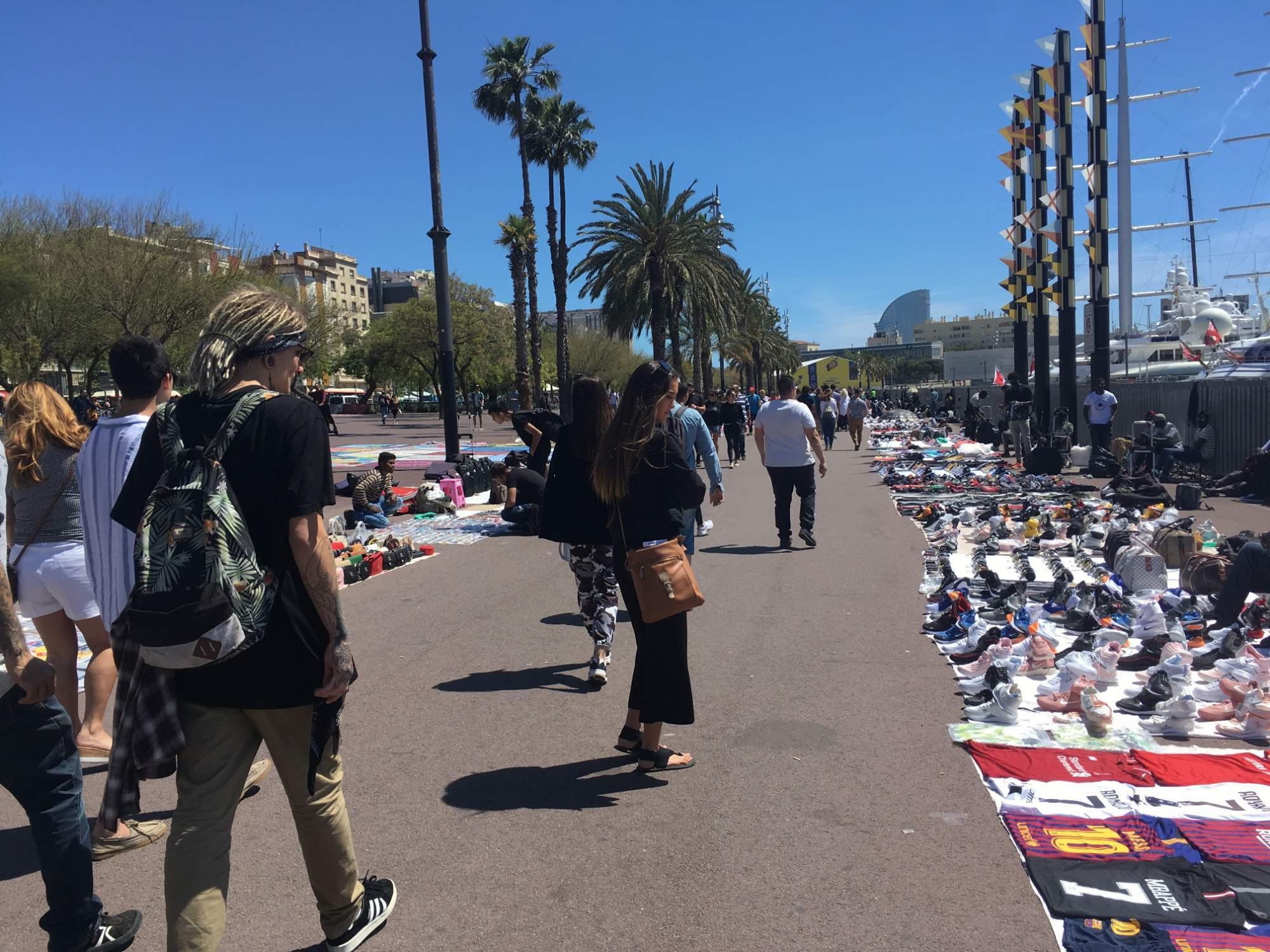 Pouliční prodejci na promenádě cestou k pláži Barceloneta