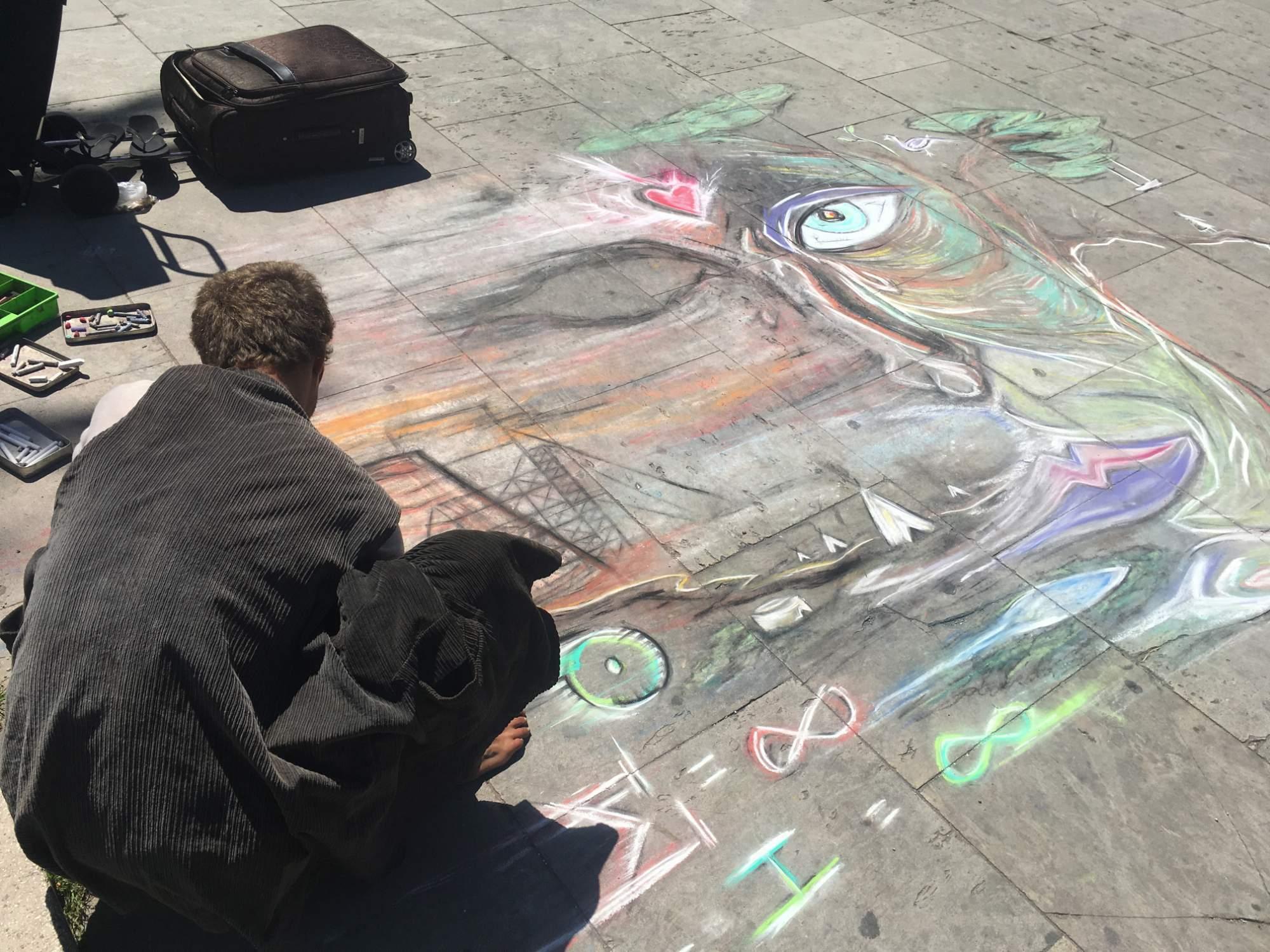 Pouliční umělec na promenádě u Vítězného oblouku