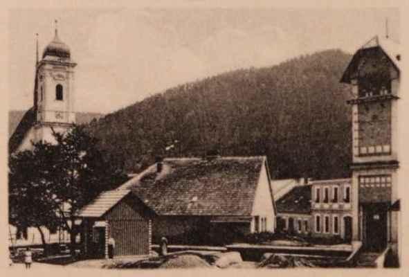 za potokem je vidět historická Sýsova kovárna - dnes zde stojí budova Svazarmu. Trafika v popředí byla v padesátých letech přestavěna a sloužila ke shromažďování mléka do výkupu. Tato budova byla odstraněna v roce 2001.