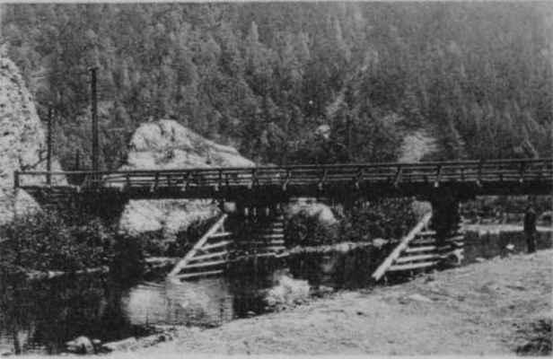 Dřevěný most přes řeku Svratku. V levé části snímku proražený koridor železnice rozděluje velké a malé Brdo. Tento most plnil svoji úlohu až do roku 1966, kdy byl 18. prosince otevřen nově postavený železobetonový most.